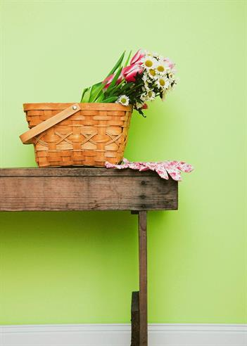 basket sitting on a table in front of a green wall