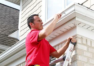 Handyman installing gutters to a house