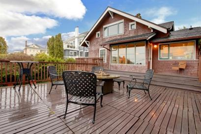 Brick home with a wooden deck and patio furniture