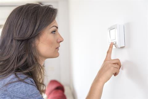 woman operating a thermostat