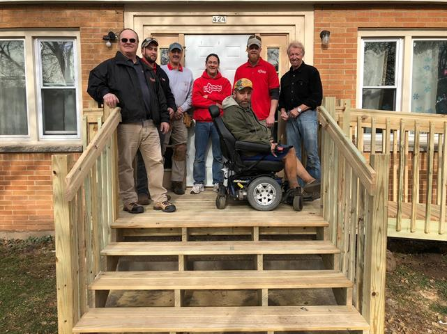 group of men standing with veteran in wheelchair on newly built porch