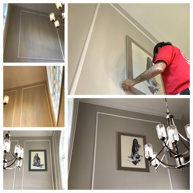 Man mounting painting to gray wall  - a Recently Complted Project