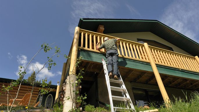 Man on ladder working on home