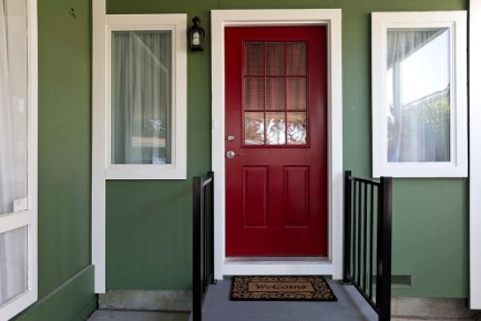 A green exterior and red door to a home