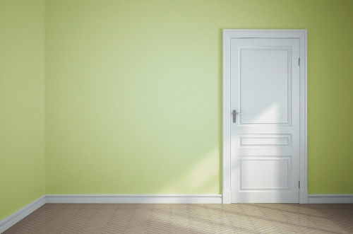 Empty room with yellow walls and a white door