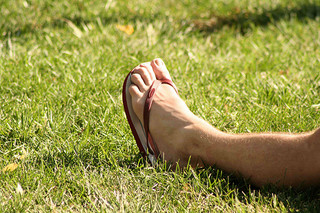Foot with flip flop on grass