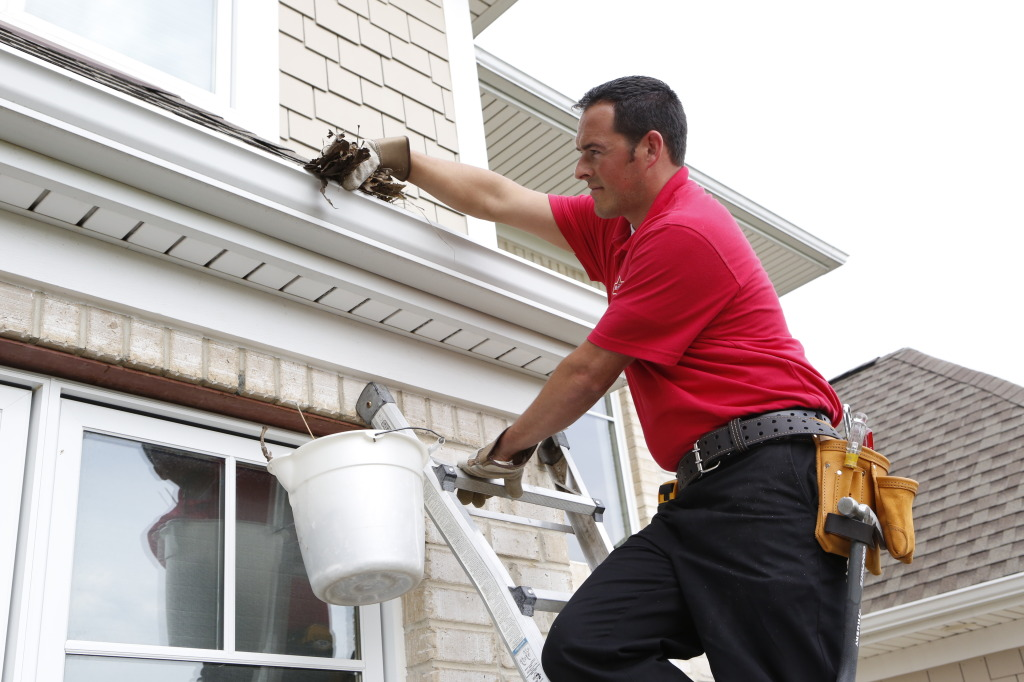 Handyman cleaning out a gutter