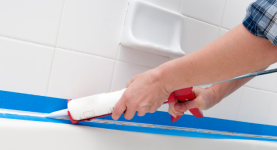 Hands caulking a tub