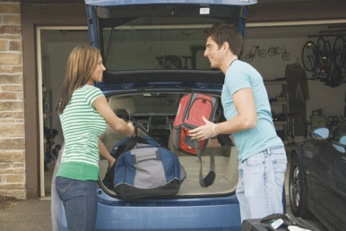 Couple packing the the trunk of their car